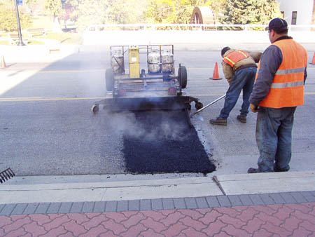 Asphalt heated and raked prior to rolling